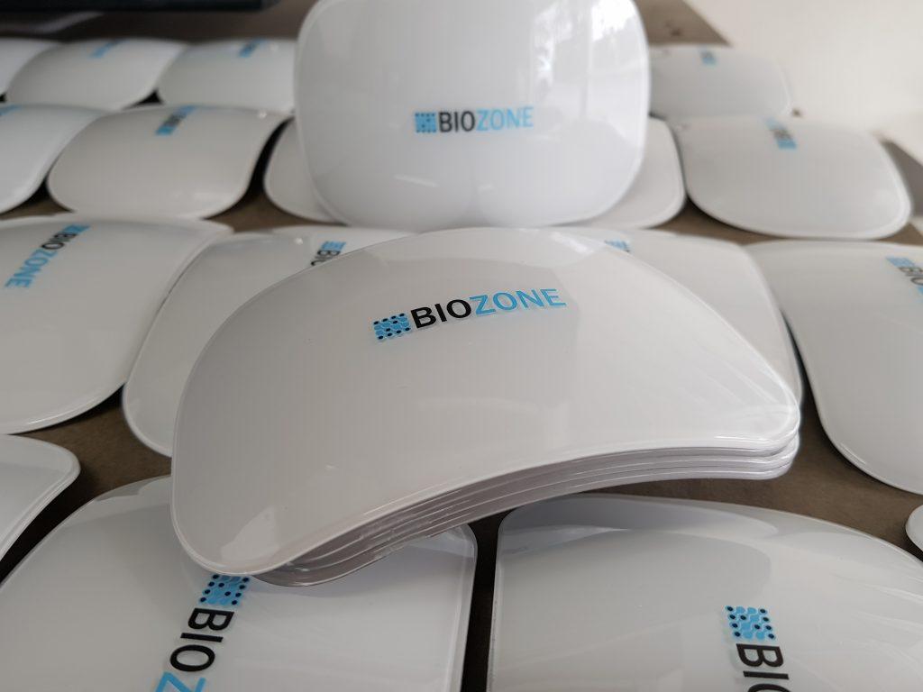 สกรีนโลโก้ Biozone ลงบนพลาสติกสีขาว ผิวโค้ง